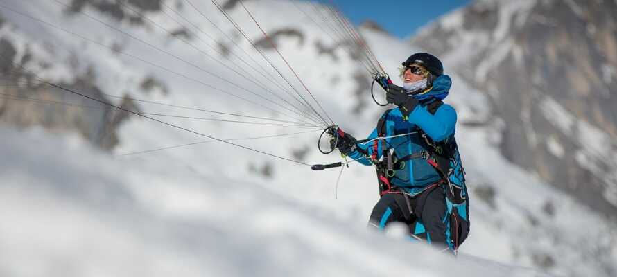 I Werfenweng er der mange spændende aktiviteter om vinteren. Prøv eksempelvis paragliding i snebelagte omgivelser.