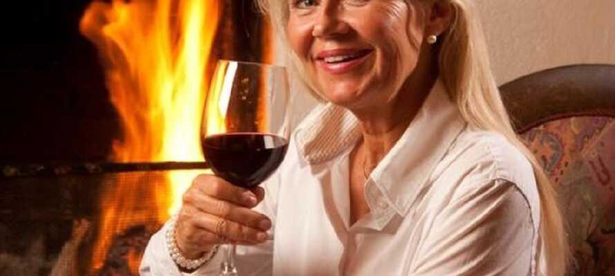 Slå deg ned med et glass vin foran peisen og spis en god middag på hotellet