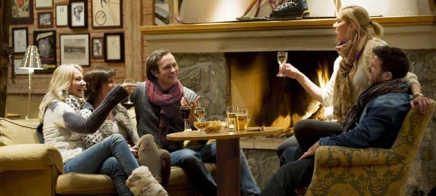 Nyd et glas vin eller en drink foran pejsen i godt selskab efter en begivenhedsrig dag i sneen.